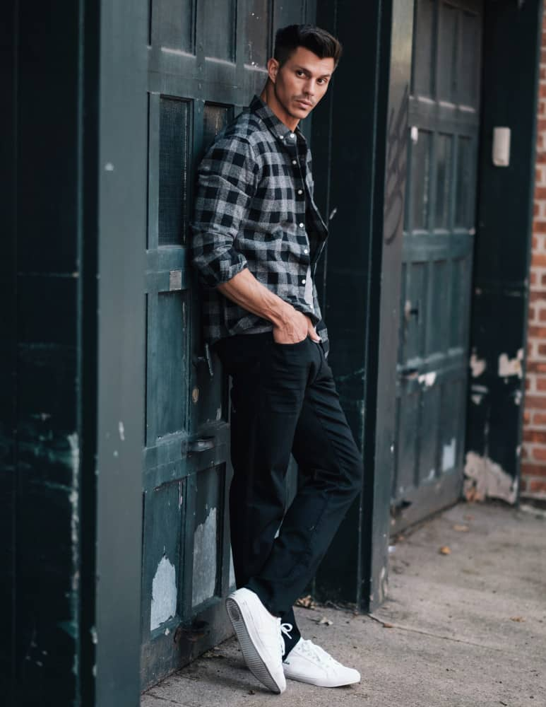 Kenny Braasch modeling a black and gray flannel shirt, black jeans, and white shoes while leaning against a garage door.