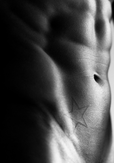 Kenny Braasch abs and star tattoo close-up in black and white.