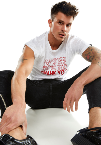 Kenny Braasch modeling white shirt with red 'Thank You' print, black pants, and black shoes while sitting.