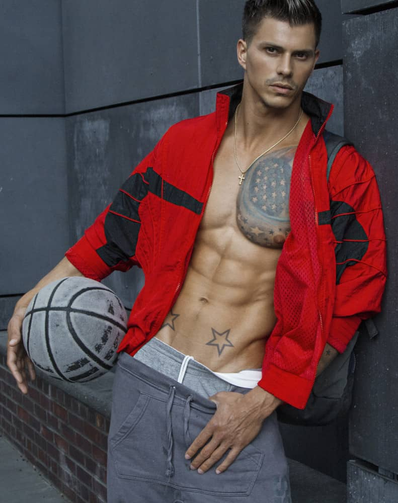 Kenny Braasch modeling an open red jacket and two pairs of gray sweatpants with chest showing and holding a basketball.