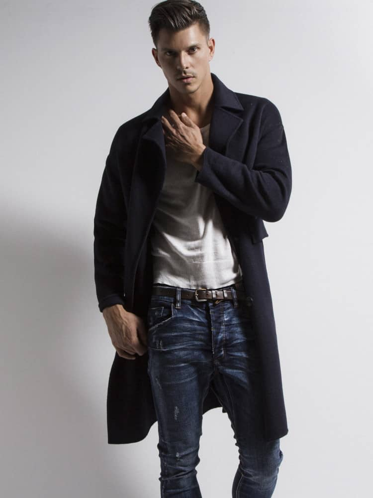 Kenny Braasch modeling navy blue peacoat, white shirt, and blue jeans.