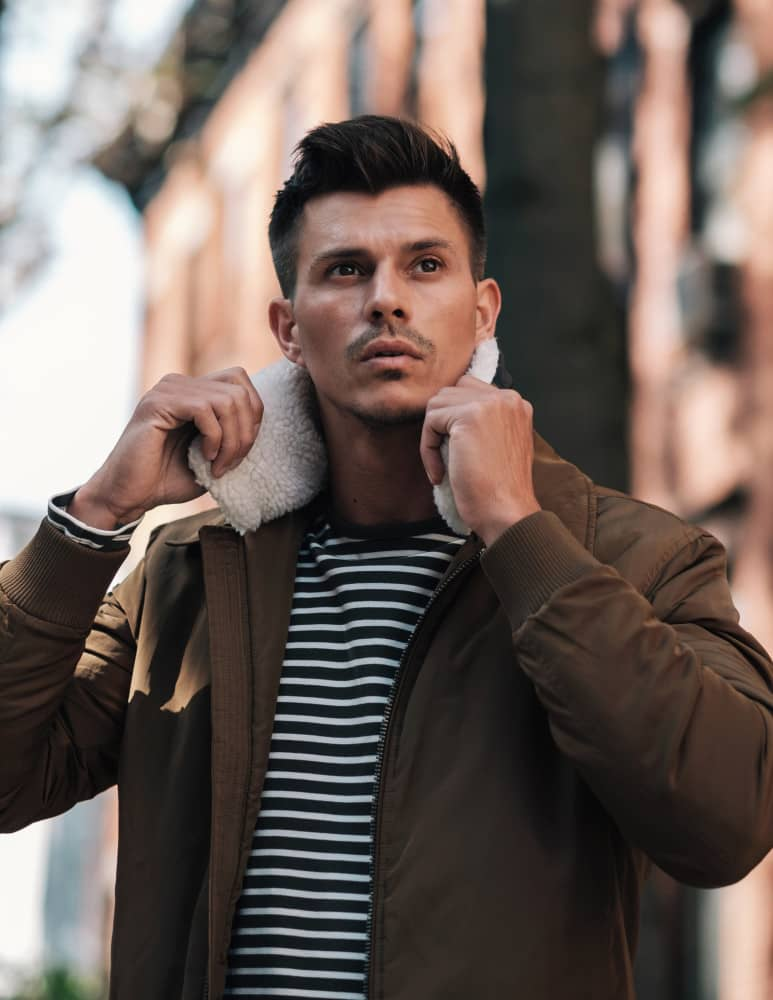 Kenny Braasch modeling a brown shearling coat and striped shirt.