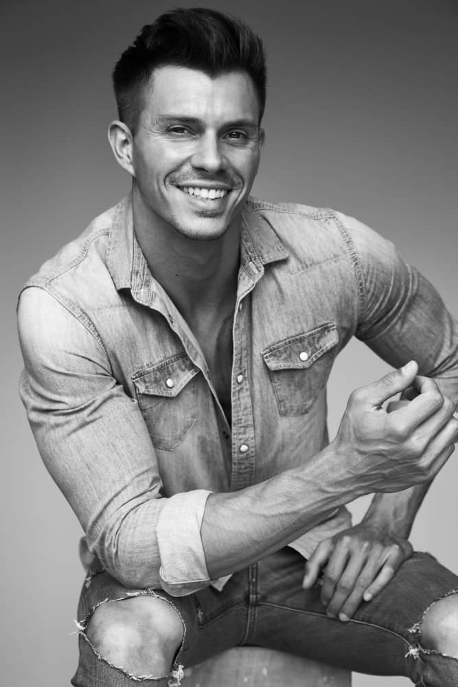 Kenny Braasch modeling an open jean shirt and jeans in black and white.