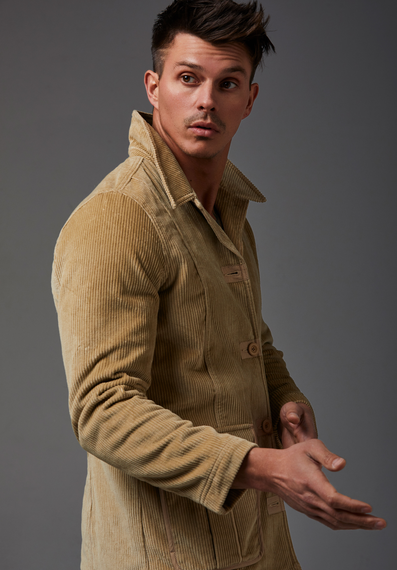 Kenny Braasch modeling a long brown corduroy coat.